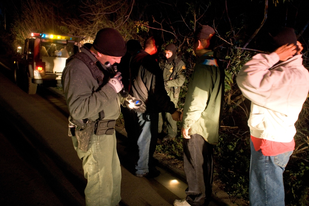 Border Patrol agents conduct pat downs of migrants caught crossing the border illegally in the Imperial Valley Sector.
